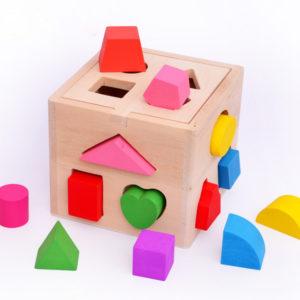 Jeu pour enfant d'insertion de formes en bois dans une boite trouée